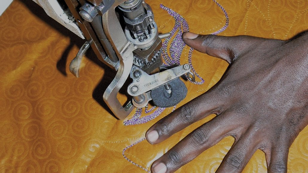 A dark Sudanese woman's hand is spread over some fabric while she sews decorative stitching on a sewing machine.