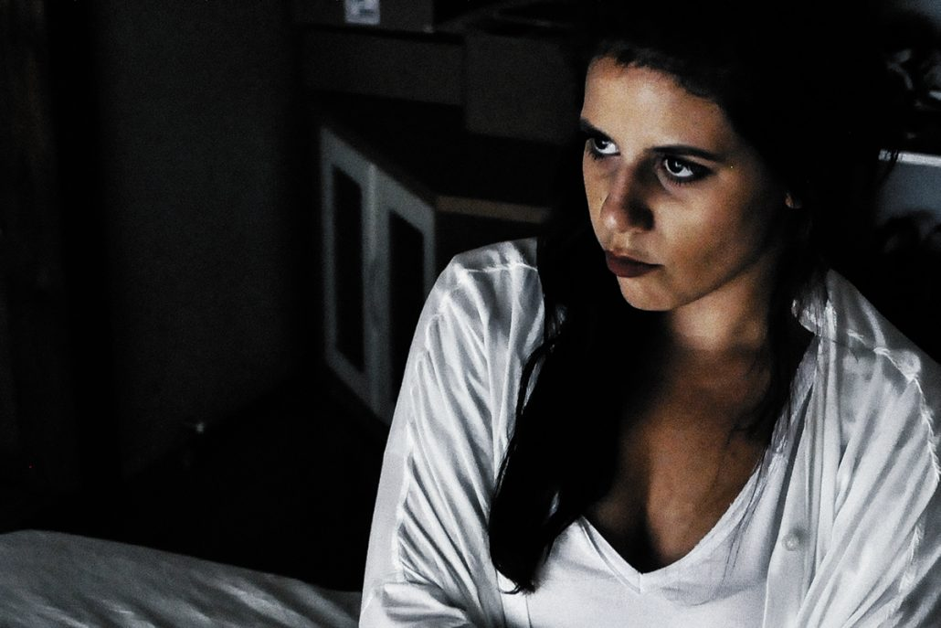 A woman with dark hair sits hugging a pillow and looks out to middle distance. She looks depressed. The room is dark apart from the light onto her white shirt and the sheets on the bed she sits on.