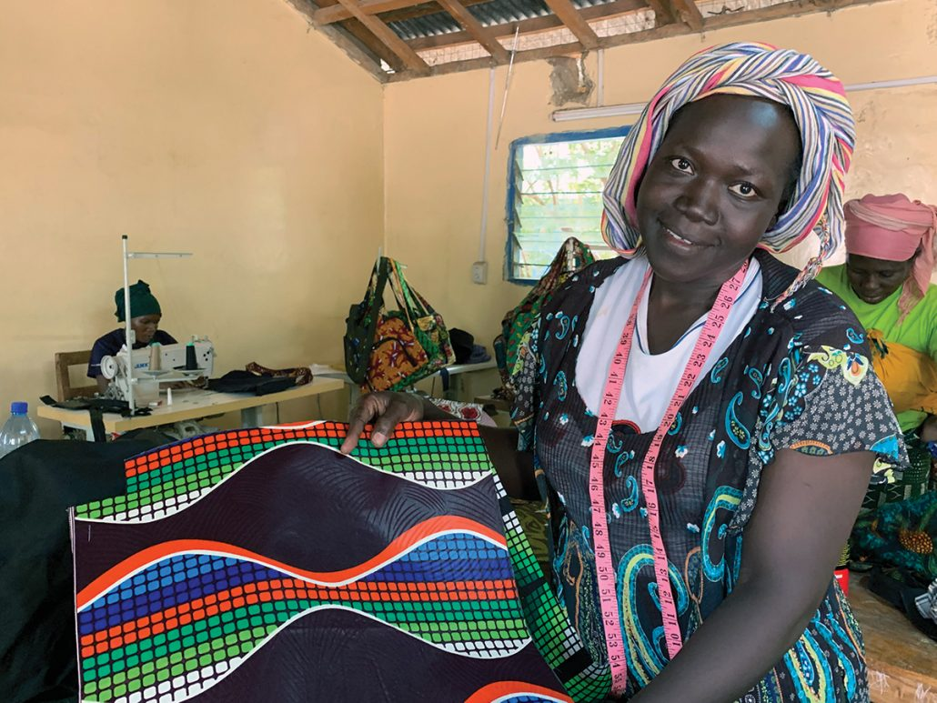 Kenyan Refugee Agnes is pictured wearing a colourful dress and head scarf, and holding a piece of colourful fabric. She is in a room where others are sewing at sewing machines.