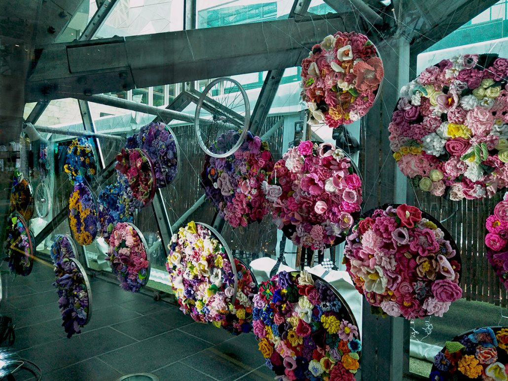 A display of colourful knitted and crocheted flowers is displayed hanging in a window. The flowers are gathered together in discs the same size as a bicycle wheel. Bicycle wheels are also hung amongst the discs.