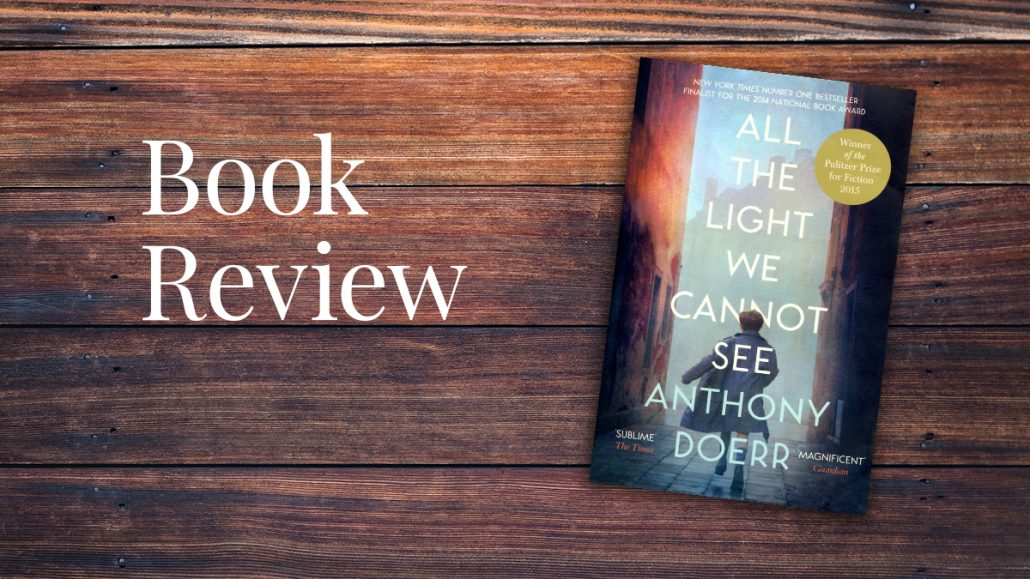 "The book 'All the Light We Cannot See"" is pictured on timber table top."