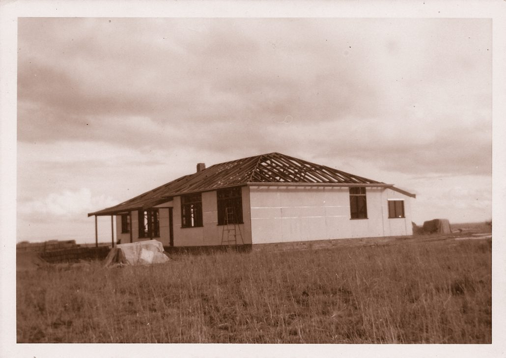 A newly constructed home of the 1940s stands isolated in a dry farm field. The photo is sepia toned.