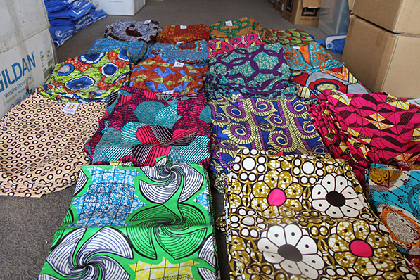 Stacks of brightly coloured and patterned fabric bags are arranged on the floor, surrounded by packing boxes.