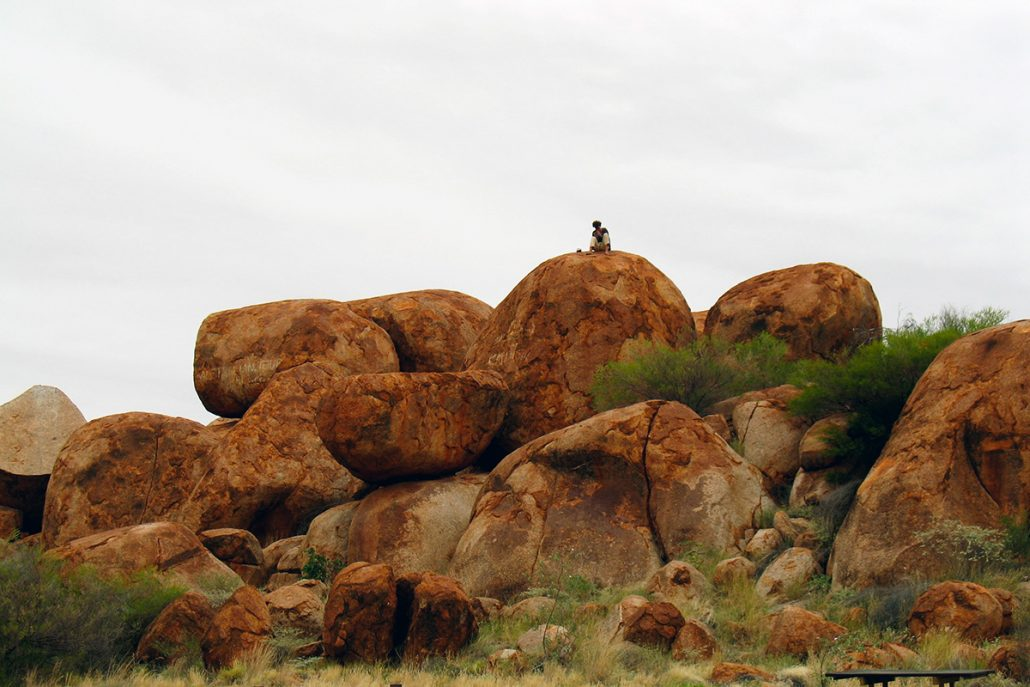 A woman sits atop some red rock formations many metres in the air. She sits in contemplation of the view. From Central Australia.